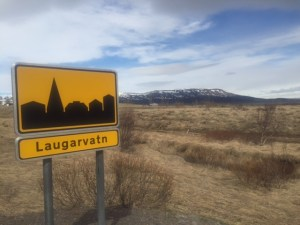These signs indicate that you're entering into a town (with the town name below the cityscape). When you're leaving a town, you'll see the same sign with a line through the silhouette.