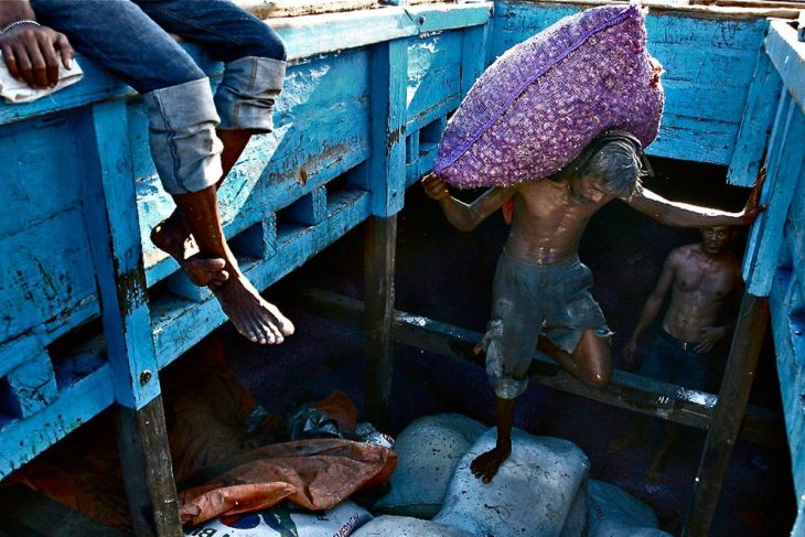 east-asia-and-pacific-winner-a-workers-carries-sacks-of-onions-from-a-ship-to-a-track-to-be-transported-to-makassar-paotere-indonesia