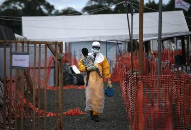a-doctors-without-borders-health-worker-in-protective-clothing-carrying-a-child-suspected-of-having-ebola-in-the-groups-treatment-center-on-oct-5-in-liberia-750x511