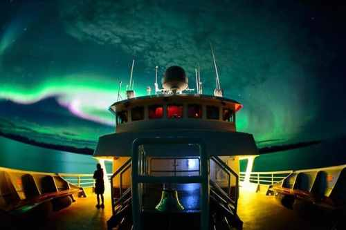 The National Geographic Sea Bird sails under a spectacular display of northern lights in Glacier Bay National Park, Alaska. The red light visible through the windows of the bridge is used to preserve the captains night vision while reading nautical charts. Is seeing the northern lights on your bucket list? @natgeocreative