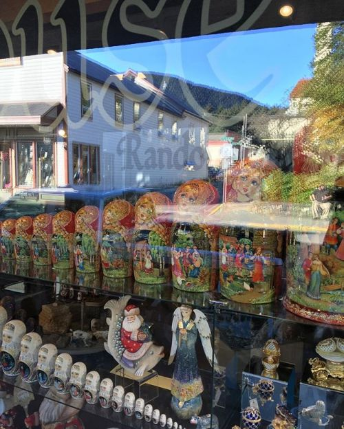 The main street of Sitka, Alaska is reflected in the window of a store selling Matryoshka dolls that speak to the Russian history of the town. Settled by the Russians in 1799, Sitka was transferred to US control in 1867 after the Alaska purchase. @natgeocreative @lindbladexp