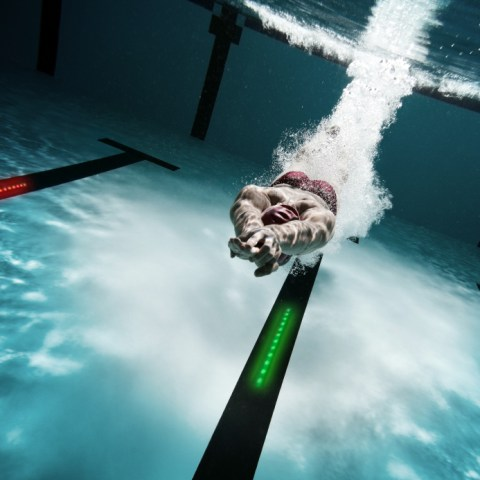 Underwater shot of a swimmer diving after the jump in the swimming pool.  This photo contains noise as a result of very low light conditions and strong post processing