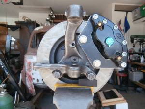 "Pictured is the Dodge Dakota spindle with a Dodge D150 brake rotor and a Wilwood D52 dual piston caliper mounted with the bracket I designed and made. These are the biggest D52 calipers Wilwood makes with two 2"" dia. pistons. It doesn't do any good for a hot rod to go fast, if you can't stop. And with the planned diesel engine, the more brakes the better. I designed the bracket. Industrial Chassis cut them out with their plasma cutting service and I drilled and tapped the holes."