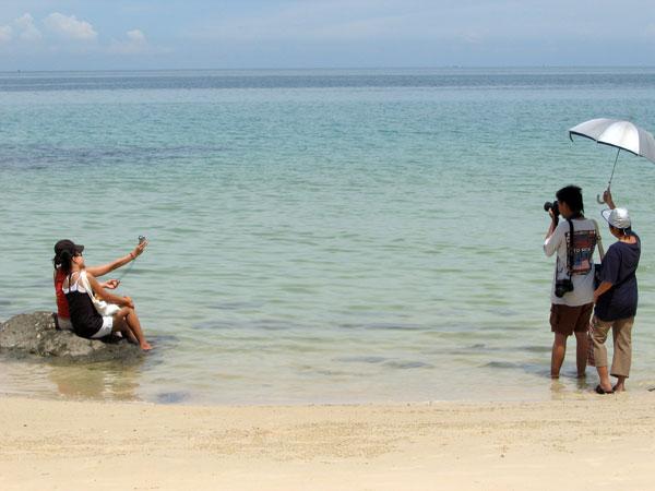 Que font des Japonais à la plage ? Ils prennent des photos.