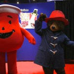 Costume Specialists shows off its lightweight, inflatable Kool-Aid man costume, while Paddington waves a hello