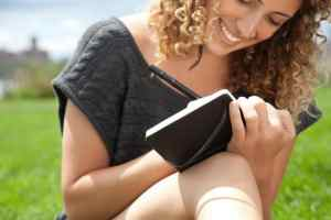 Young woman in park, writing in notebook