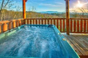 Hot tub on the deck of a Gatlinburg TN cabin rental with a scenic mountain view.
