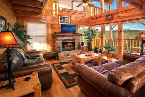 The beautiful family room of a Gatlinburg TN cabin rental with a fireplace and flatscreen TV.