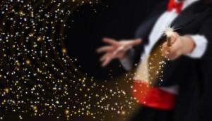 A magician waving a wand at a magic show.