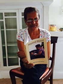 Mom reads Beyond Blood, Alchemus Prime's fifth book. She is on the cover holding Anaya, her granddaughter beyond blood.
