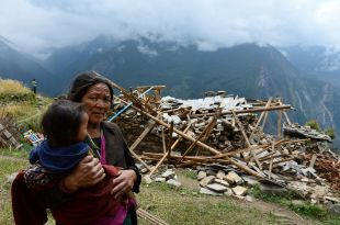 A mother carries her son in Uiya village, in northern-central Gorkha district, on April 29. Hungry and desperate villagers rushed toward relief helicopters in remote areas of Nepal, begging to be airlifted to safety, four days after a monster earthquake killed more than 5,000 people. (Photo: Sajjad Hussain, AFP/Getty Images)