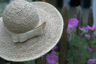 My gardening hat resting on the fence surrounding my cottage garden
