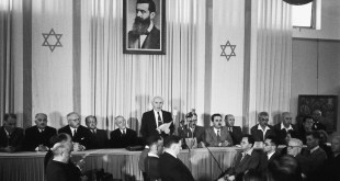 David Ben-Gurion declaring independence beneath a large portrait of Theodor Herzl, founder of modern Zionism