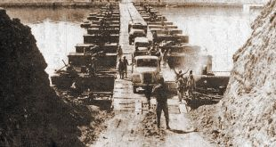 Egyptian military trucks cross a bridge laid over the Suez Canal on October 7, 1973, during the Yom Kippur War/October War = Public Domain