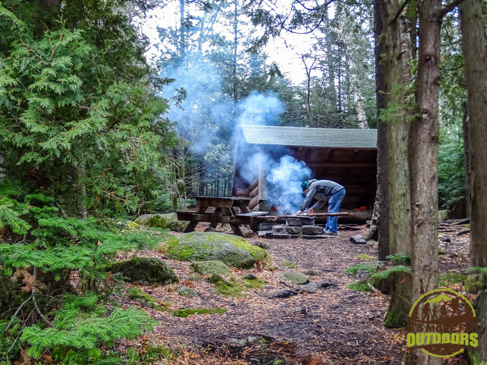 Chris getting a morning campfire going after a late November lean to campout at ADK's Wilderness Campground on Heart Lake, Adirondacks, Lake Placid, NY