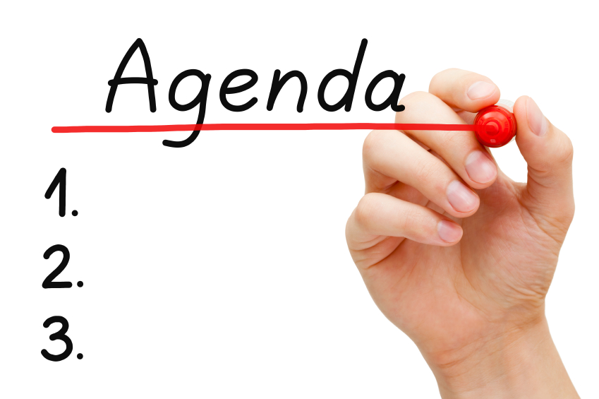 Hand underlining Agenda with red marker on transparent wipe board.