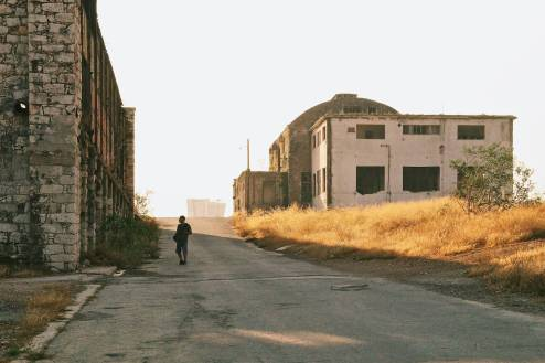 A man walking on the road by an old factory.