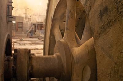 A rusty generator coupler inside an old factory.