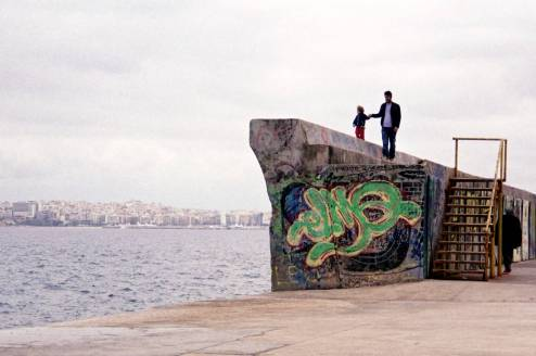 A father with his child are walking on top of a sea wall.
