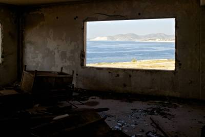 View to the sea from the window of and abandoned office building.
