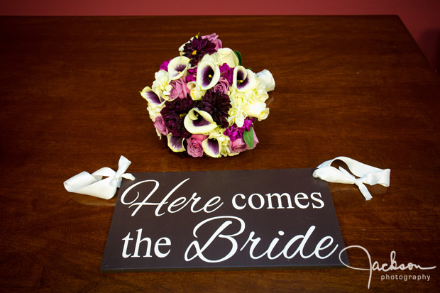 bridal bouquet with here comes the bride sign just married