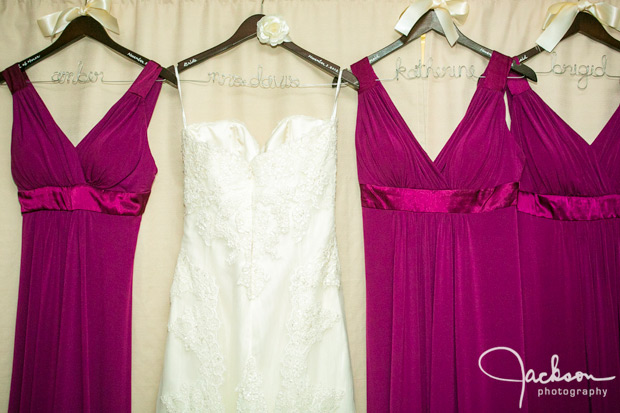 bride and pink bridesmaid dresses hanging on named hangers