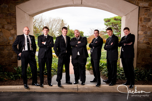 groom and groomsmen under archway