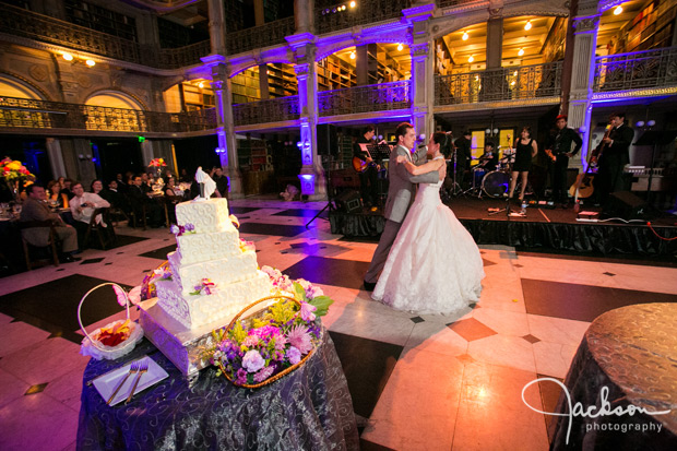 bride and groom first dance by wedding cake