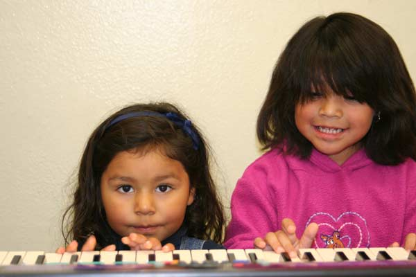 Beautiful little girls playing the keyboard together
