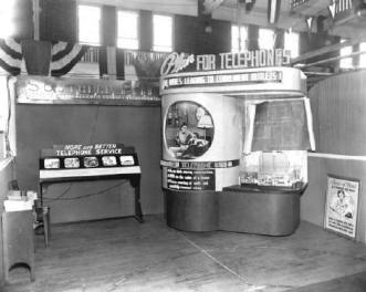 """""""Plan for Telephones,"""" admonished this 1949 Jacksonville display from Southern Bell. The round picture on the stand showed a middle-age couple using a rotary phone. The signs also alluded to """"wires leading to convenient outlets"""" and """"peace of mind all through the night."""" This exhibit appears to have been set up on an indoor basketball court."""