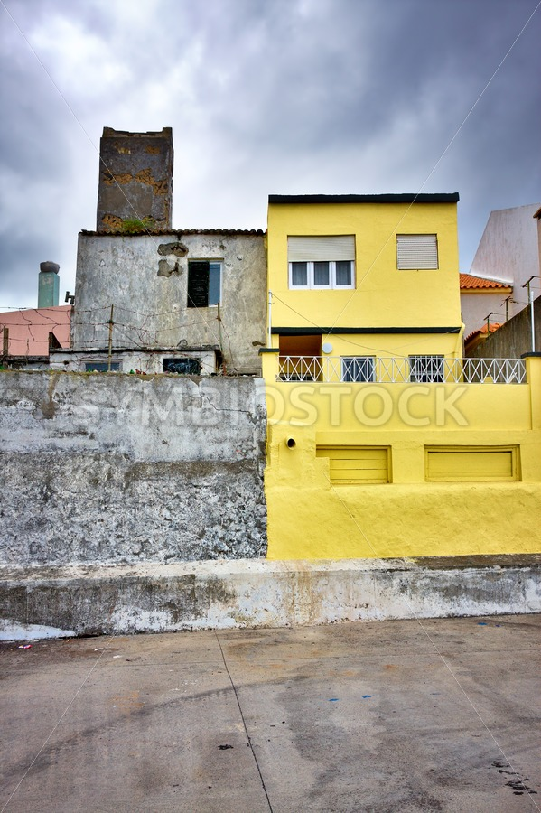 Colorful yellow house dark clouds - Jan Brons Stock Images