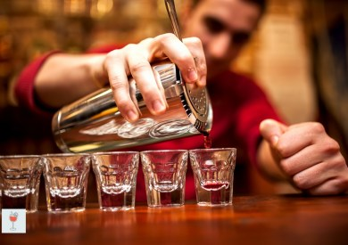 barman hand with shake mixer pouring beverage into glasses on bar