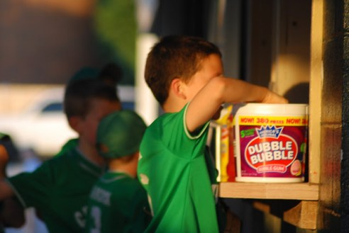 Boy in a green jersey reaching for Dubble Bubble