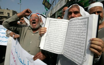 Muslims protesting with a Quran