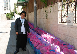 Liora Tedgi standing beside Ohr Meir U'Bracha care packages.