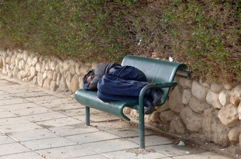 Homeless person sleeping on a bench in Beer Sheva