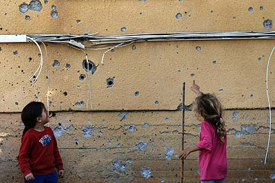 Young Kibbutz girls Kibbutz examine the shards on the wall by a qassam rocket.