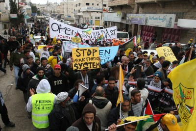 Palestinian demonstrators, joined by Israeli and foreign peace activists, shout slogans during a demonstration