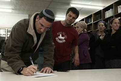 A Migron settler signs the relocation agreement, March 11, 2012.