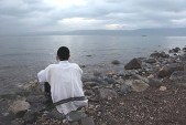 Young Jewish man meditating by the shore of the Kinneret.