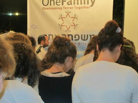 Participants in OneFamily's Yom Hazikaron event observe a minute of a silence