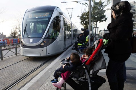 A Palestinian woman and her children wait for the Jerusalem's Light Rail, at the Shuafat station in north Jerusalem.