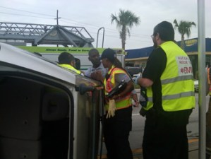 Miami Hatzalah members assist firefighters at accident scene.