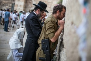 Jews, a Haredi and a soldier, pray next to each other at the Western Wall.