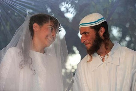 Newlywed couple Harel and Talya David under the Chupa in Karnei Shomron in Judea and Samaria. The new &quot;Tzohar Law&quot; will empower couples to seek officiating by non-Haredi rabbis.