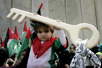 A Palestinian child holds a key made of wood, symbolizing the key of a home lost during the creation of the state of Israel