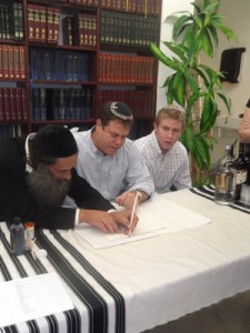 "Usher Bryn, brother of Rabbi Dovid Bryn, z""l, fills in a letter together with his son Jonathan."