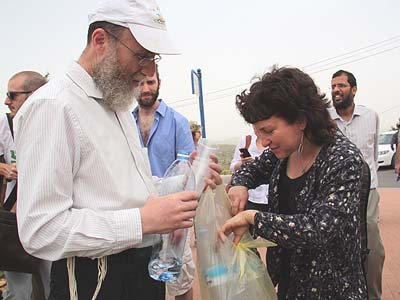 Meretz activist receiving cold water from a settler.