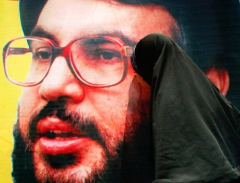 A Palestinian woman kisses a poster of Hezbollah leader Hassan Nasrallah
