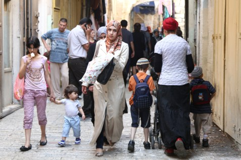 A Jewish family pass an Arab family in the Arab quarter of the Old City of Jerusalem